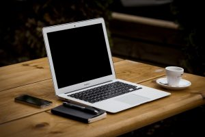 A laptop on the desk to use and do good research when you are finding a perfect home in Nashua, NH.
