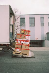 A pile of moving boxes next to a moving truck.
